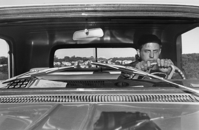 Black-and-white photograph of the artist at the wheel of a pickup truck
