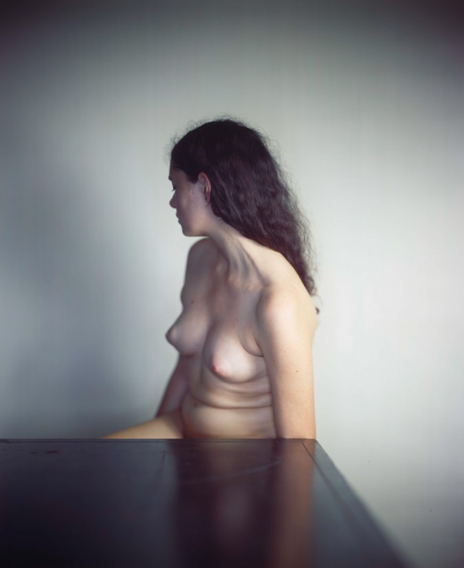 Color photograph of a nude white woman seated behind a table, turned away from the camera.