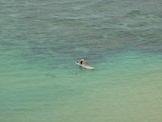 Color photograph of a person bending backwards on a surfboard in a shallow blue-green sea