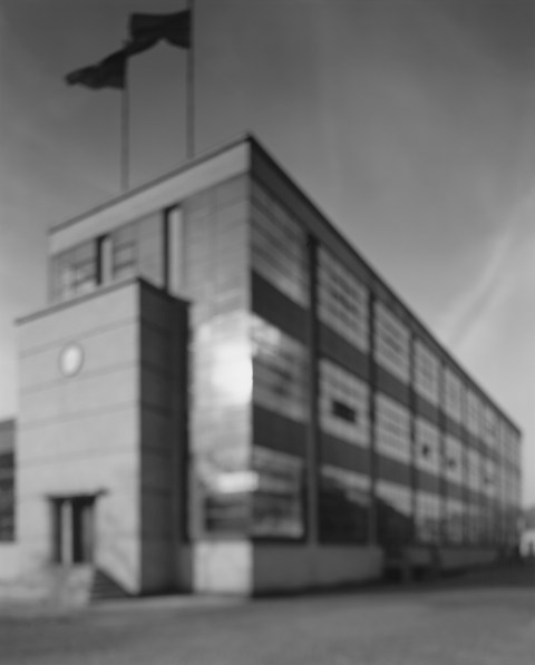 Black-and-white photograph of out of focus factory building with rows of large glass windows and two flags on the roof