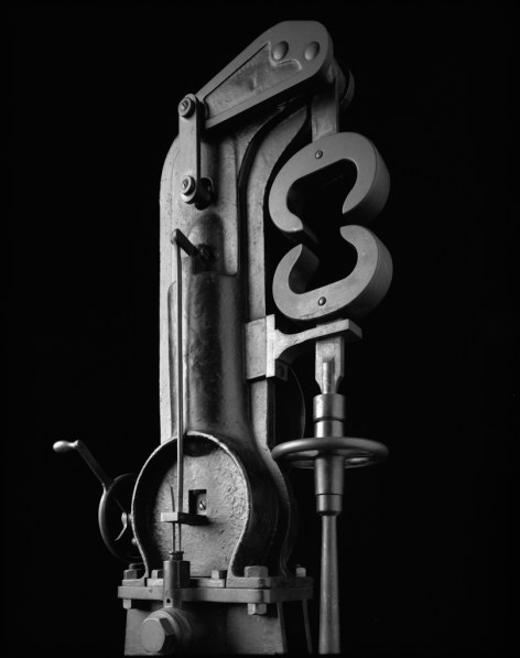 Black-and-white photograph of a metallic mechanism with a piston and claw-like forms