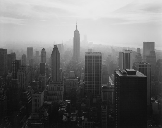 Black-and-white photograph of a city skyline centered on the Empire State Building looking downtown