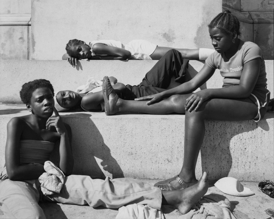 Black-and-white photograph of four children reclining on stone steps in the sun