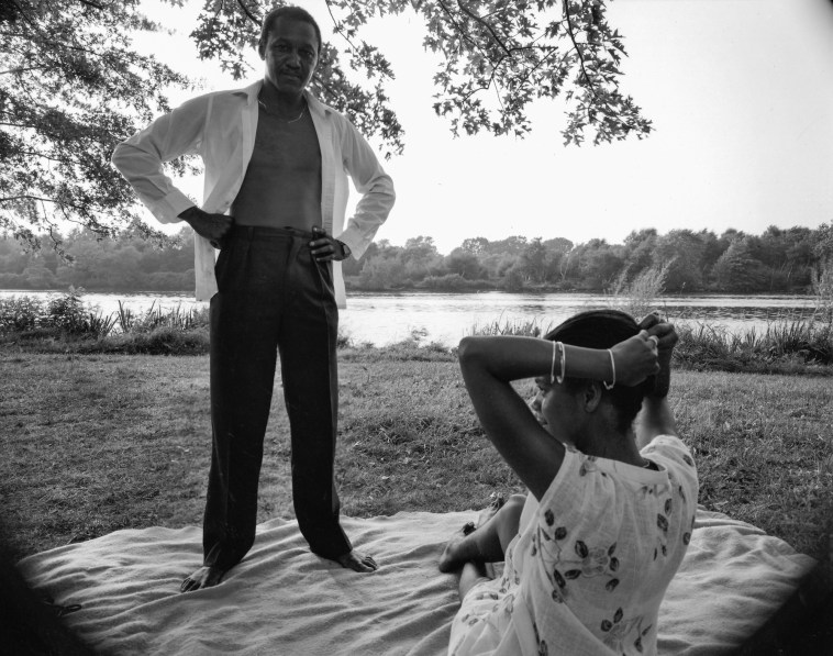 Black-and-white photograph of a man standing with his hands on his hips on a picnic blanket over a woman putting up her hair