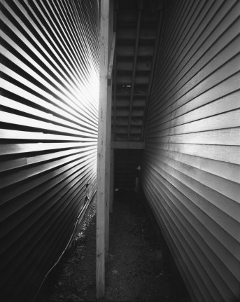 Black-and-white photograph of a stairway from beneath between two clapboard walls