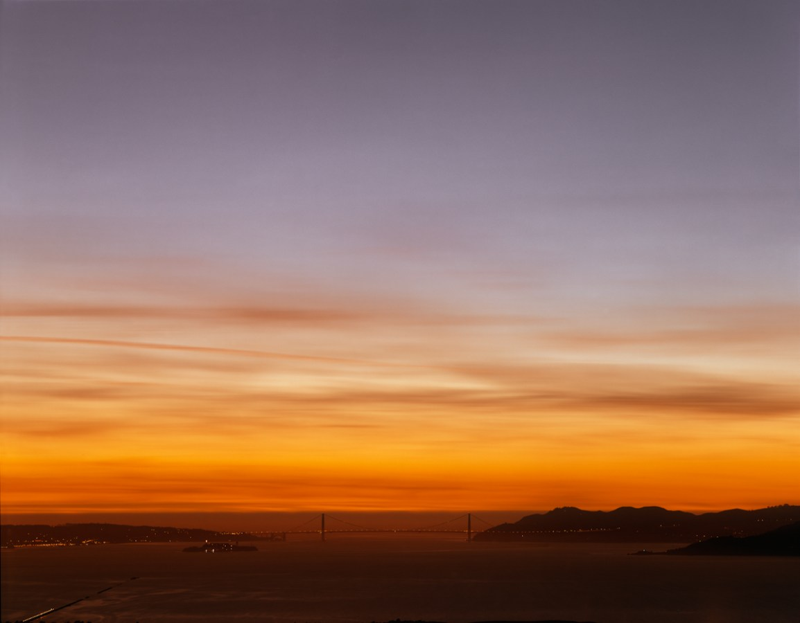 Color photograph of the Golden Gate Bridge on the horizon under a bright red-orange and violet sunset