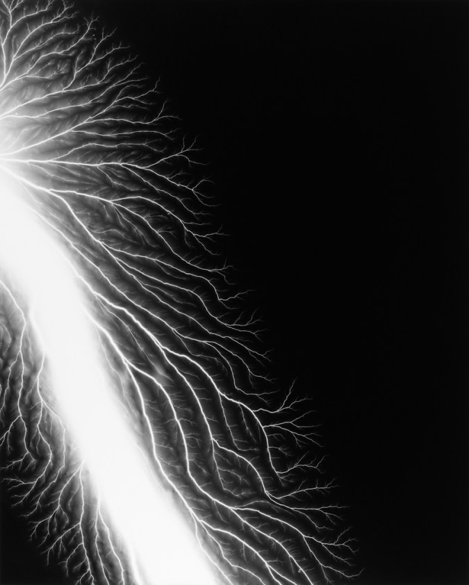 Black-and-white photograph of a white trail of light in the bottom left corner with smaller branches coming off of it on a black background