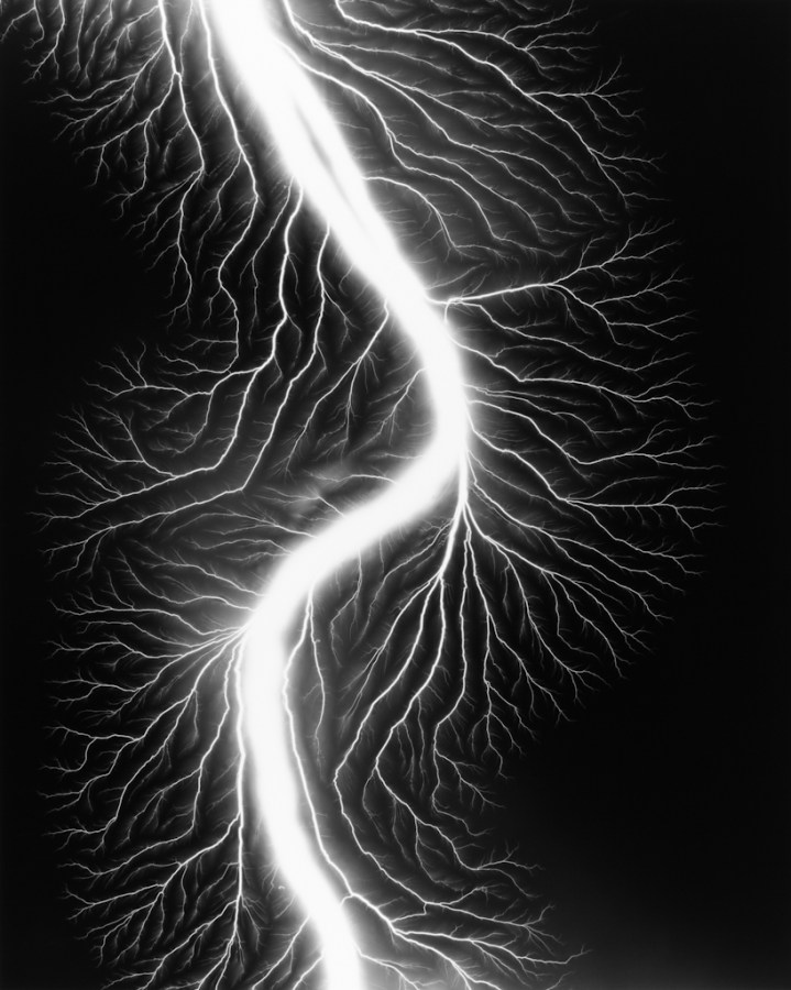 Black-and-white photograph of a white curving trail of light with smaller branches coming off of it on a black background