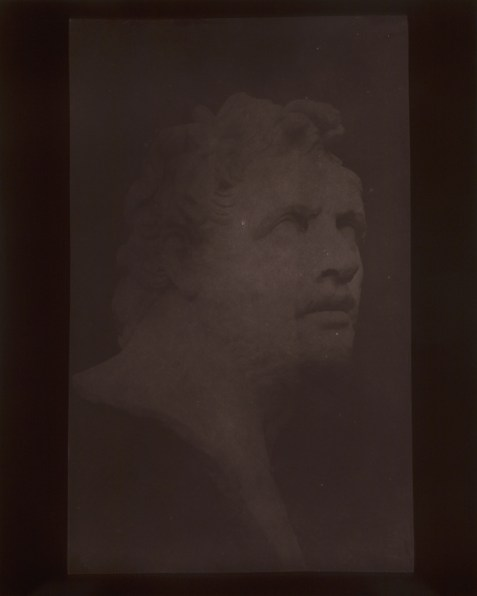 Brown-toned photographic three-quarter view of a stone sculpture of a man