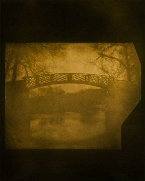 Yellow-toned photograph of a foot-bridge under bare trees