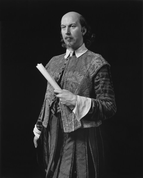 Black-and-white frontal three quarter of a wax figure of a man in a brocaded outfit holding a roll of paper to his torso