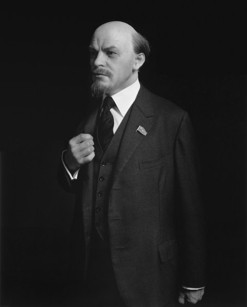 Black-and-white three quarter portrait of a wax figure of a man in a suit jacket and tie with one closed hand over his chest