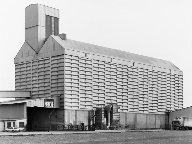 Black-and-white photograph of an industrial building against a clear sky