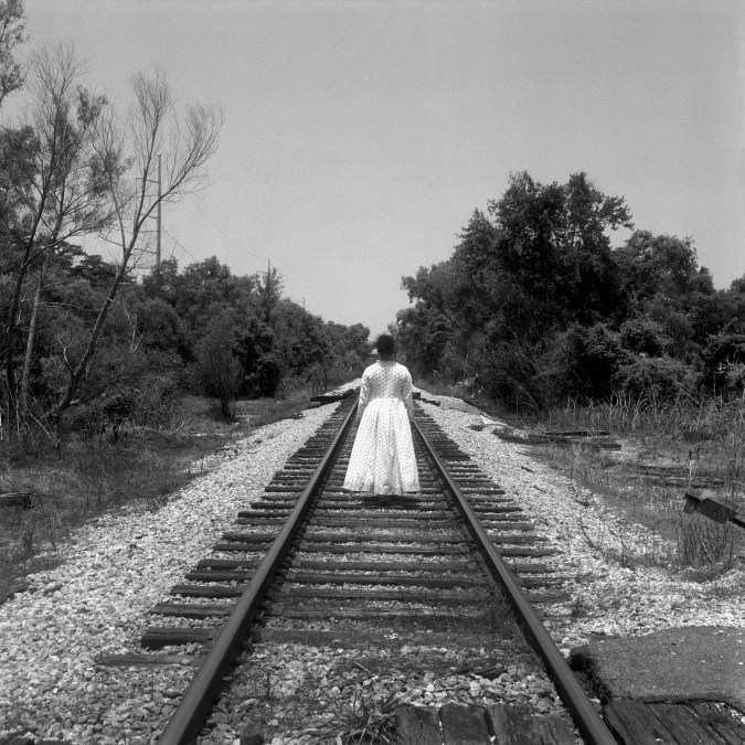 Black and white photograph of a woman clad in a long white dress walking along a railroad track receding into the horizon.