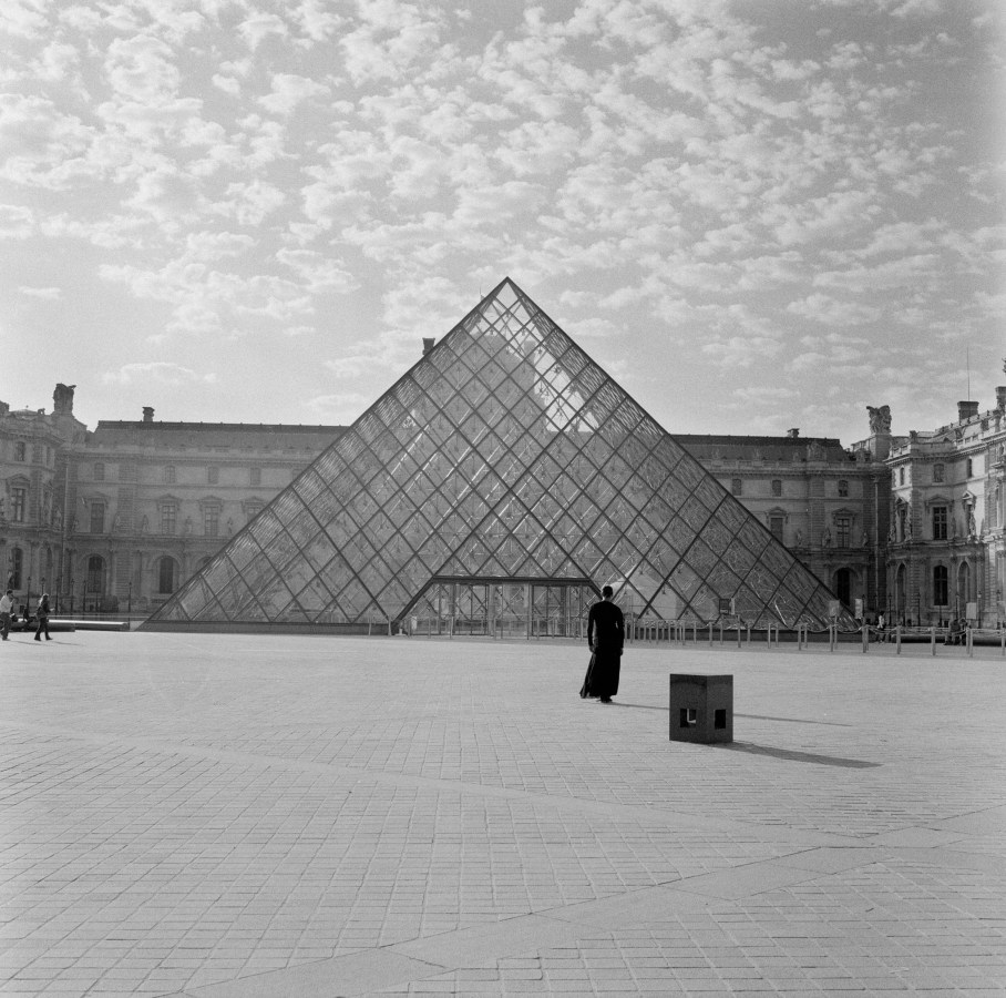 Black-and-white photograph of a black-clad figure standing in front of the Louvre Museum in Paris.