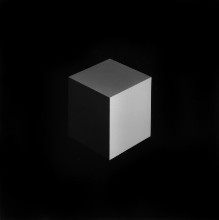 Black-and-white image of a gray cube at its vertex lit from the lower right corner on a black background