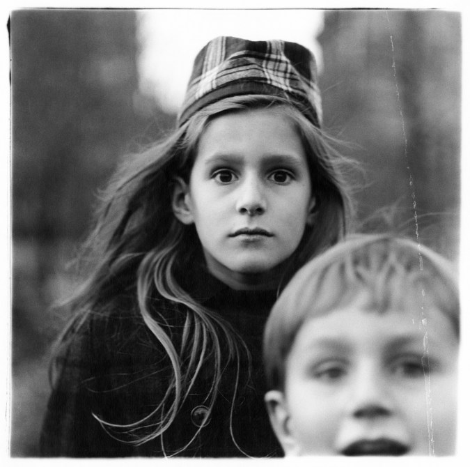 Black-and-white photograph of a girl wearing a hat and a young boy in the bottom right corner of the frame