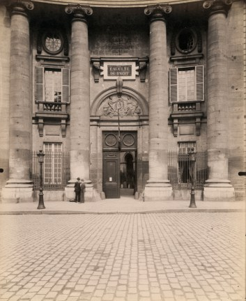 Photograph showing wooden doors with an arch and columns on a Parisian building