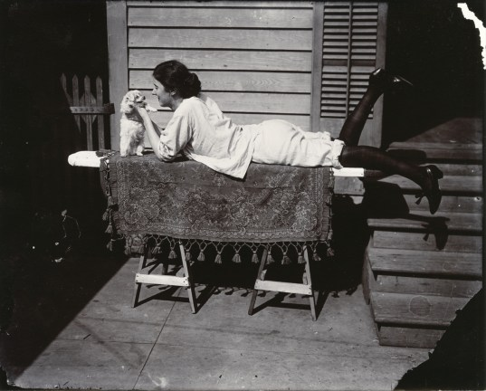 Black-and-white photograph of a woman laying on a table playing with a puppy