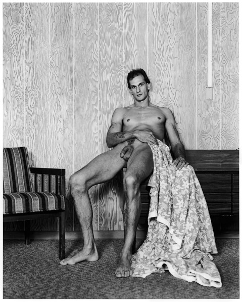 Black-and-white photograph of a nude man leaning against a wood paneled wall with a flowered blanket draped by his side