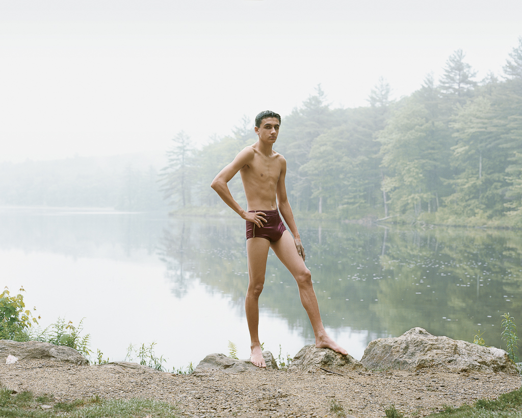 Color photograph of a young man in a bathing suit posed with his hand on his hip on the rocky shore of a misty lake