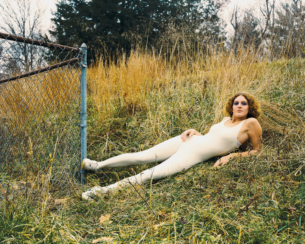Color photograph of a woman in a white bodysuit reclining on a grassy hillside next to the corner of a chainlink fence