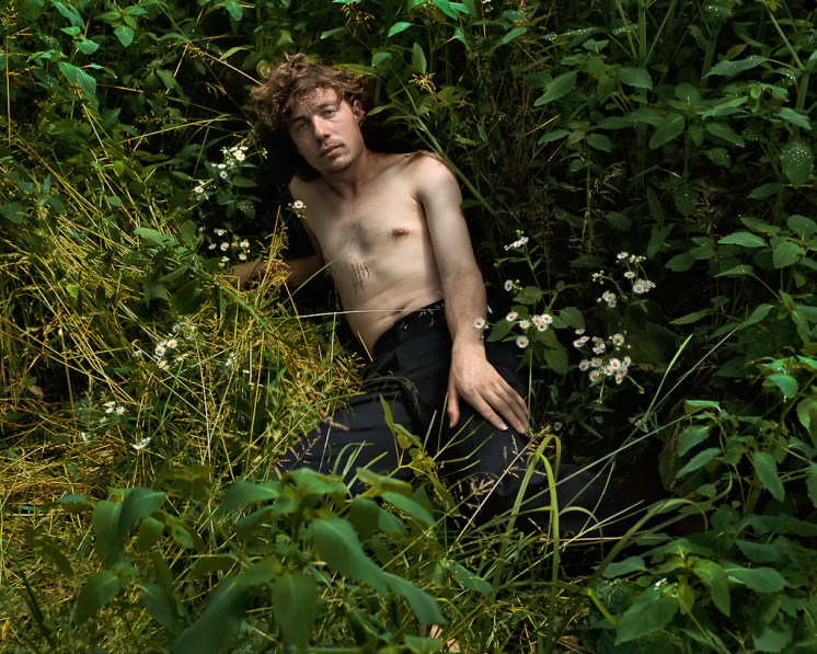 Color photograph of a shirtless man reclining in a grassy outdoor clearing