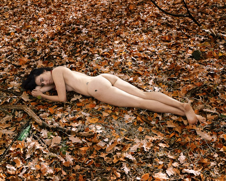 Color photograph of a nude woman lying on her stomach on a ground covered with autumn leaves