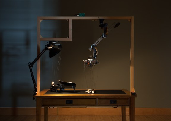 Robotic arms control a marionette playing the piano and a marionette dancing on a desktop