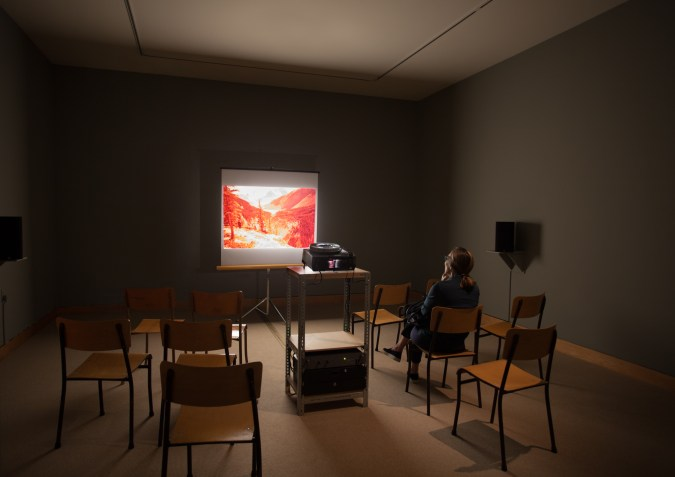 A single person in a darkened room with chairs, a slide projector, and an image of a landscape projected on the screen