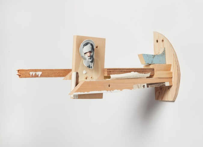 A wall mounted sculpture made of various pieces of wood with a collage of a human head on one piece of wood