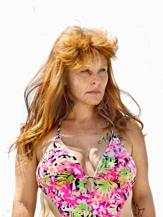 Color photographic portrait of a woman with red hair in a pink-patterned bathing suit standing against a blank white wall