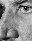 Black-and-white close-up photographic portrait of a man's eye and nose