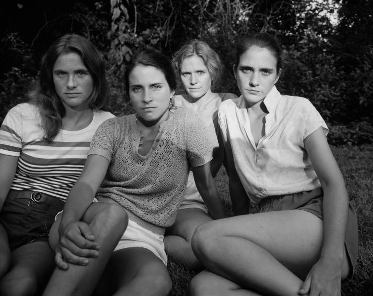 Black-and-white photographic portrait of four young women seated outdoors on grass