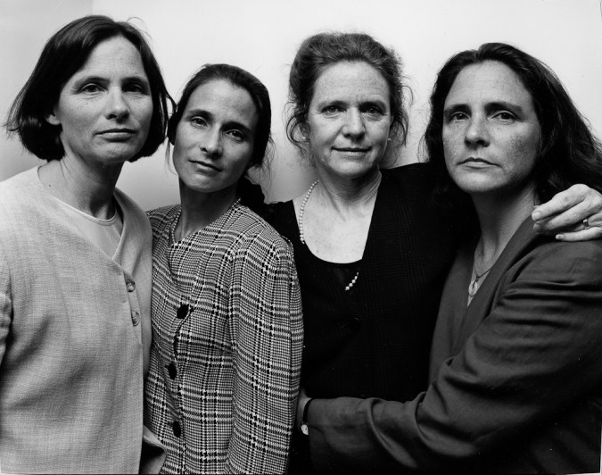 Black-and-white photographic portrait of four women with arms around each other standing in front of a blank wall