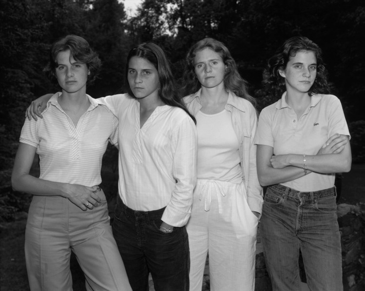 Black-and-white photographic portrait of four young women standing side-by-side outside