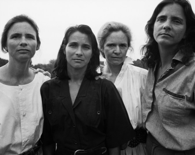 Black-and-white photographic portrait of four women standing looking slightly down at the viewer
