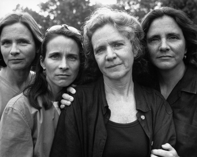 Black-and-white photographic portrait of four women standing outside
