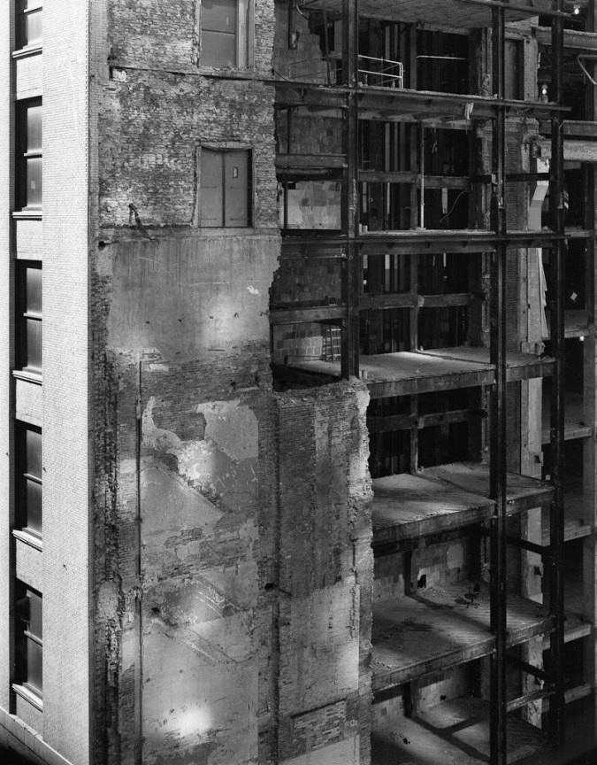 Black-and-white photograph of reflected light and shadows on a partially-demolished brick building