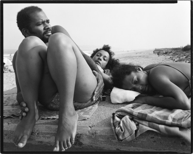 Black-and-white photograph of three young adults reclining on blankets on a beach