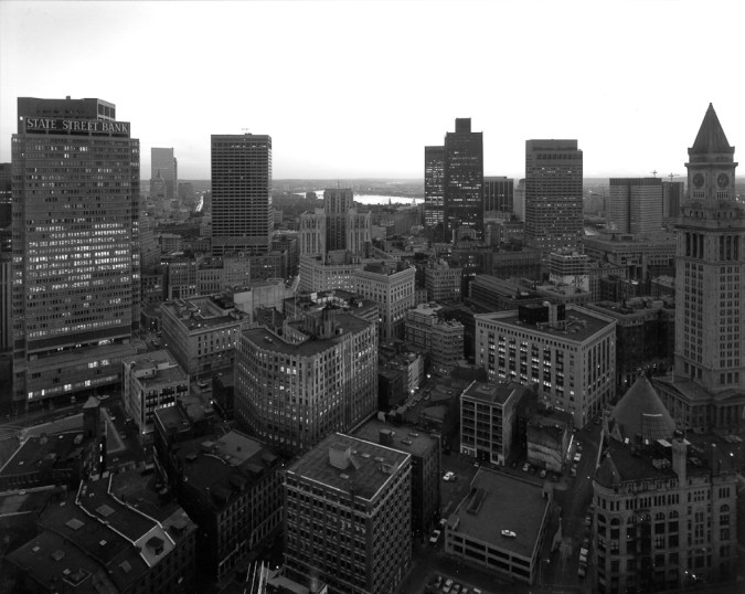 Black-and-white photograph of a city skyline with high rise buildings scattered throughout the landscape