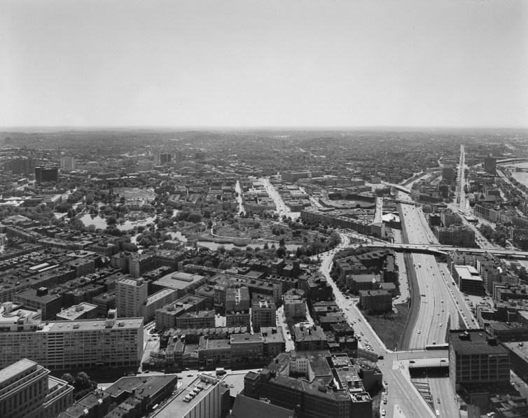 Black-and-white photograph of a highway and surrounding neighborhoods at midday under a clear sky