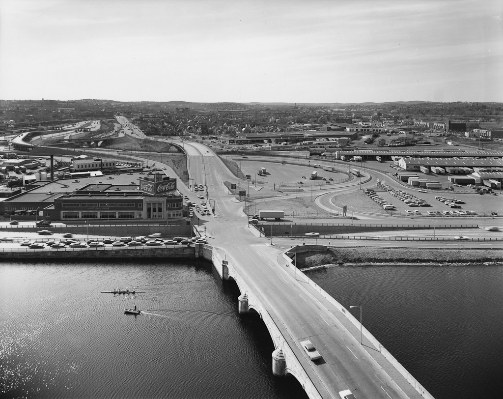 Black-and-white photograph of a highway bridge crossing a river next to a Coca-Cola plant
