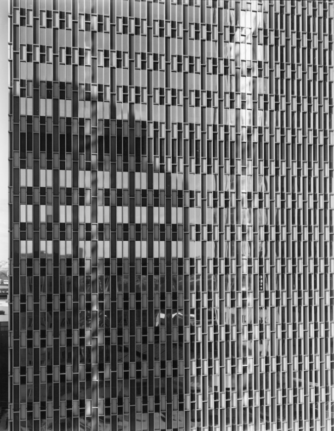 Black-and-white photograph of the glass-windowed façade of a modern office building
