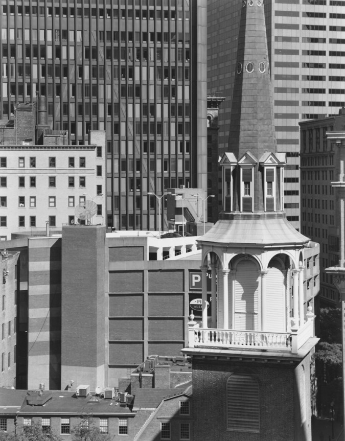 Black-and-white photograph of a steeple in front of modern high-rise buildings