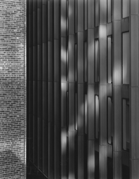 Black-and-white photograph of reflected light and shadow on a modern high-rise building façade