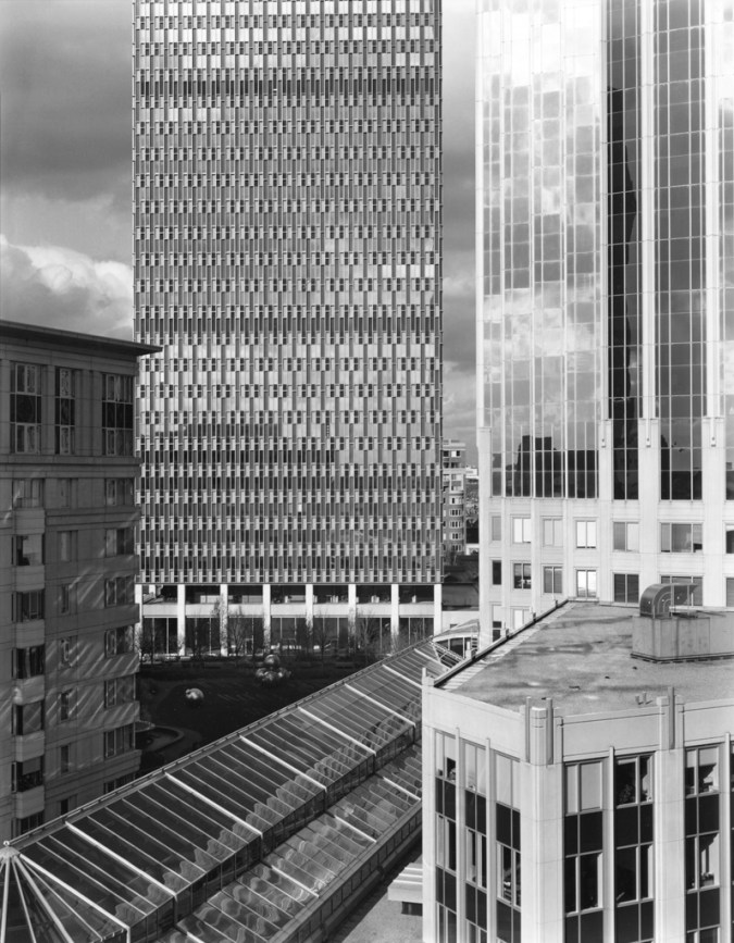 Black-and-white photograph of glass-fronted high-rise buildings under a cloudy sky