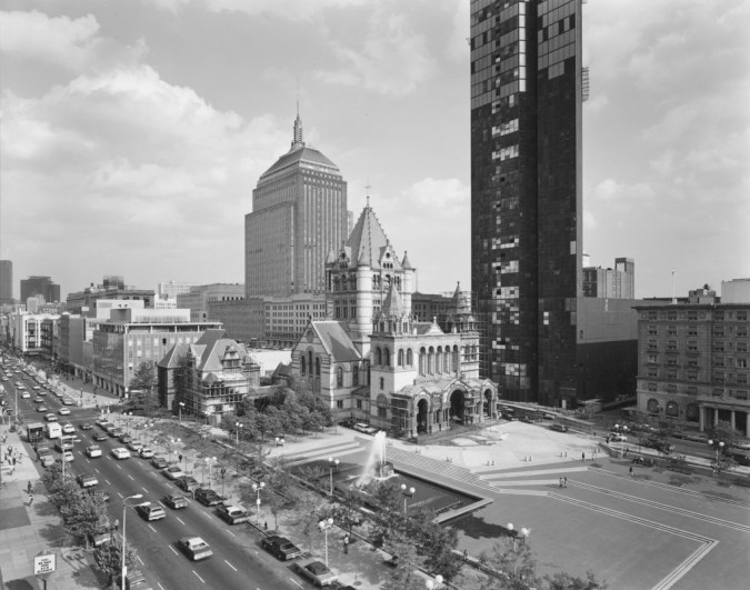 Black-and-white photograph of a large church set behind an open plaza amid modern city high-rise buildings