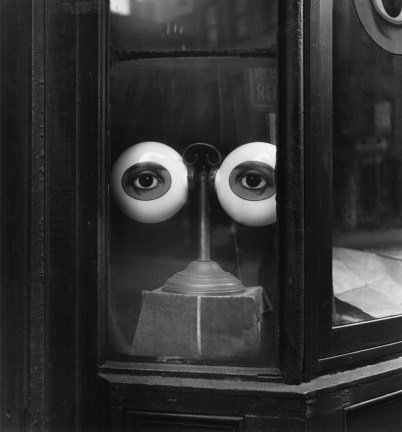 Black-and-white photograph of two model painted eyes mounted on a stand in a shopfront window