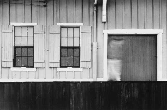 Black-and-white photograph of the façade of a clapboard building with a blurred figure passing the entryway